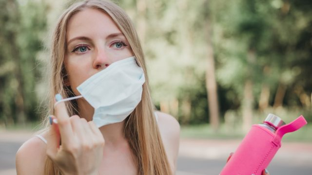 Woman taking off her respiratory mask and holding a bottle of water