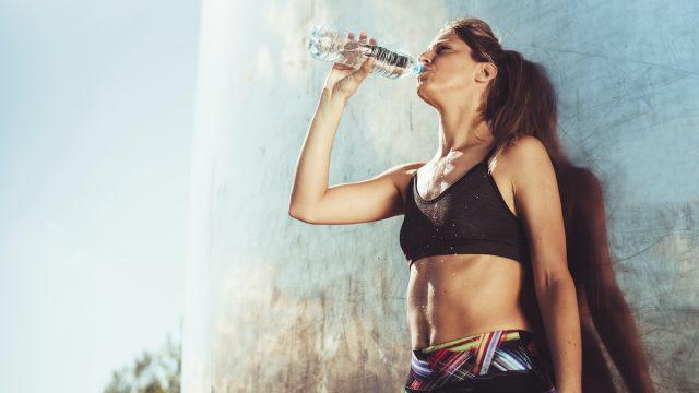 woman taking a water break during workout