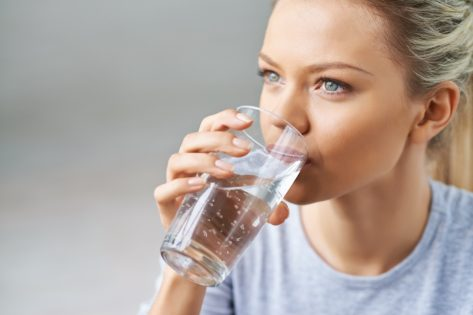 Woman drinking water from glass.