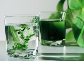 green chlorophyll water drops mixing in glass of water