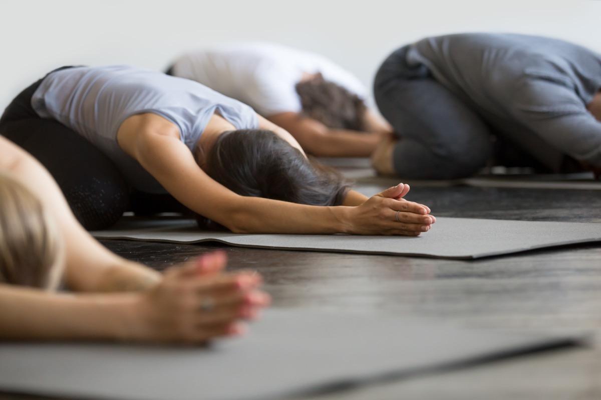 women in child's pose on yoga mat