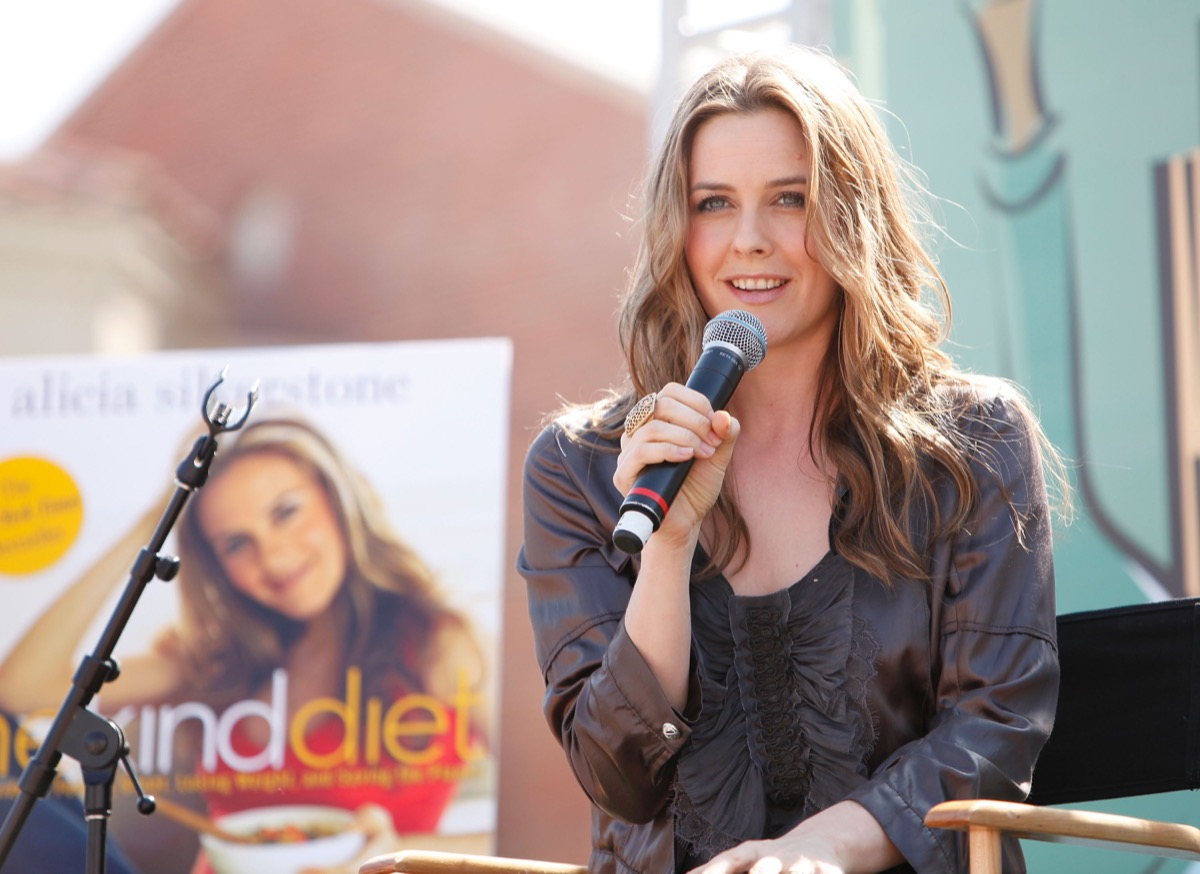 alicia silverstone talking into microphone in front of her kind diet cookbook