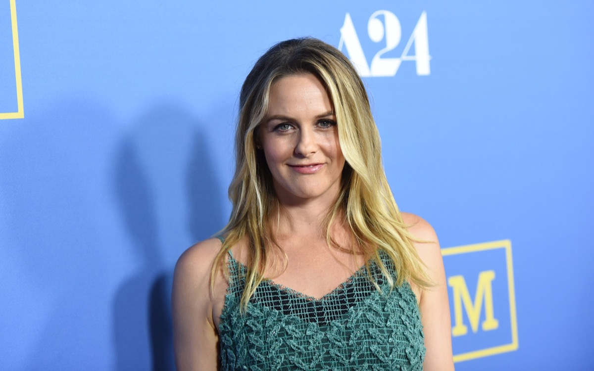 alicia silverstone smiling in green dress on red carpet