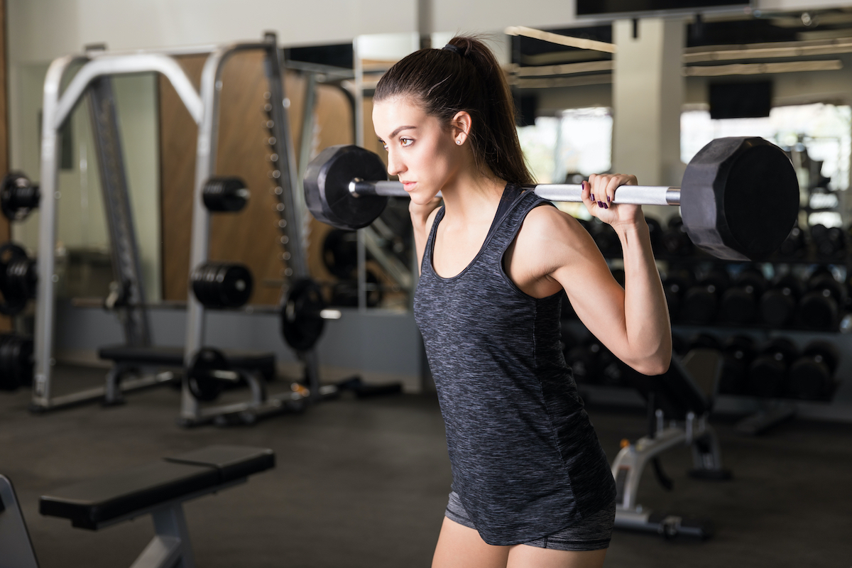 Woman full of determination doing behind the neck barbell shoulder press in health club
