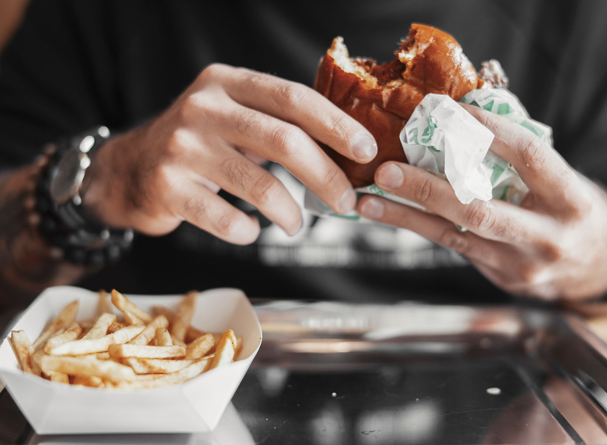 person eating burger and fries