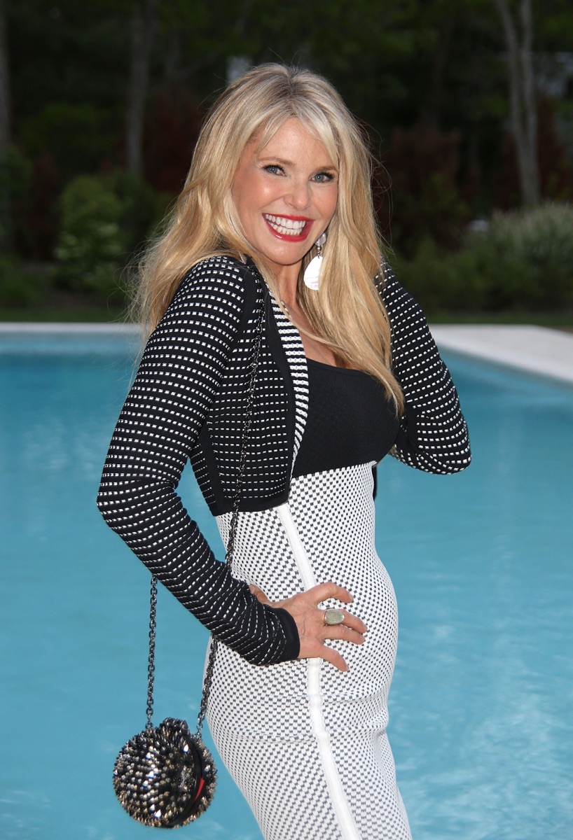 christie brinkley posing in front of pool in black top and white skirt