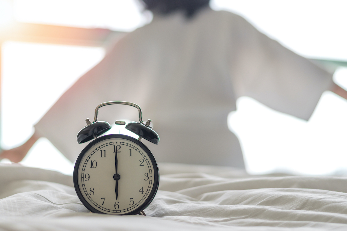 Woman on bed wake up stretching in bedroom with alarm clock at 6.00 a.m. morning. Biological Clock healthcare lifestyle concept