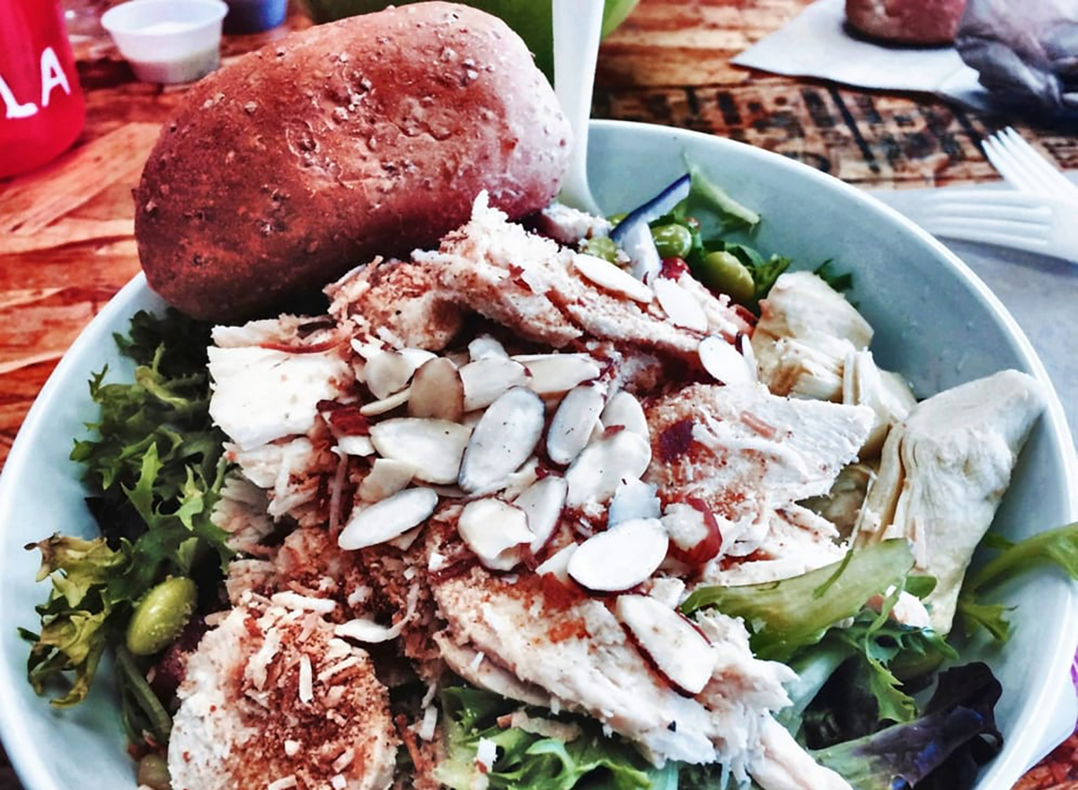 salad topped with coconut chicken and almond slivers
