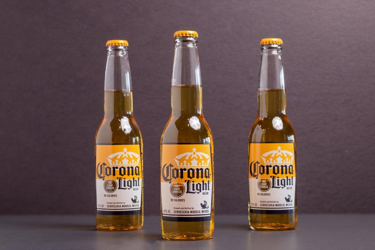 three bottles of corona light beer on gray background