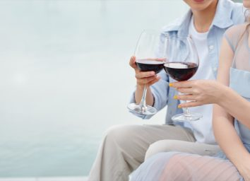 couple toasting outdoors with glasses of red wine