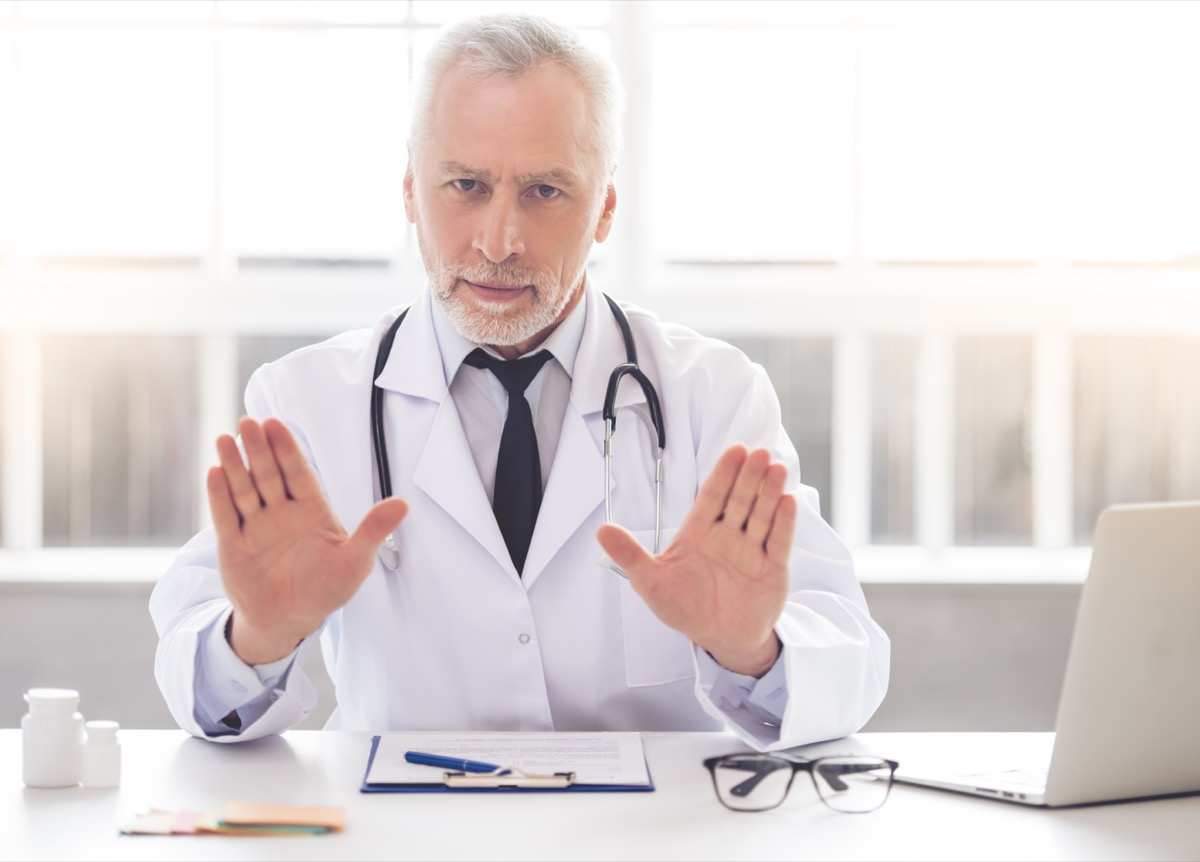 doctor in white coat is showing palms
