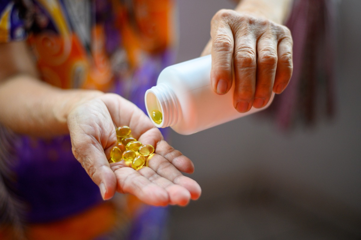 Bottle of omega 3 fish oil capsules pouring into hand.