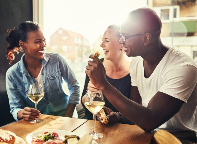 group of multiethnic friends in their 30s drinking wine outside at a table