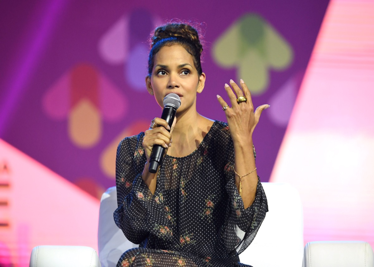 halle berry in black dress seated and holding microphone
