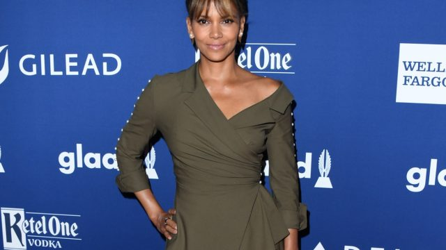 halle berry in off-the-shoulder green dress in front of glaad step and repeat
