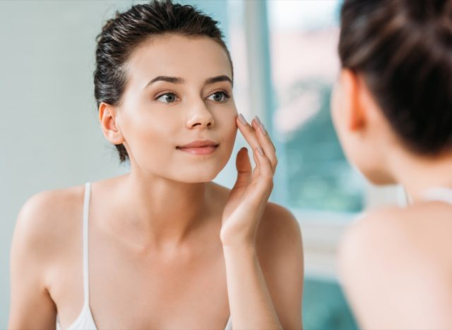 Woman touching face and looking at mirror in bathroom