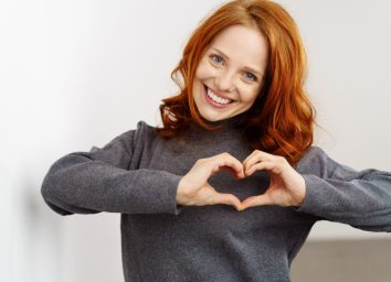 Woman making a heart gesture with her fingers in front of her chest.