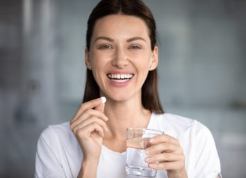 happy woman holds pill glass of water looks at camera