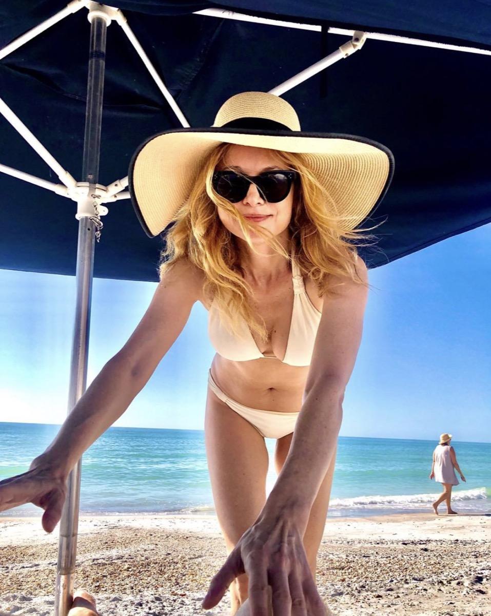 heather graham in white bikini and sun hat bending over toward camera