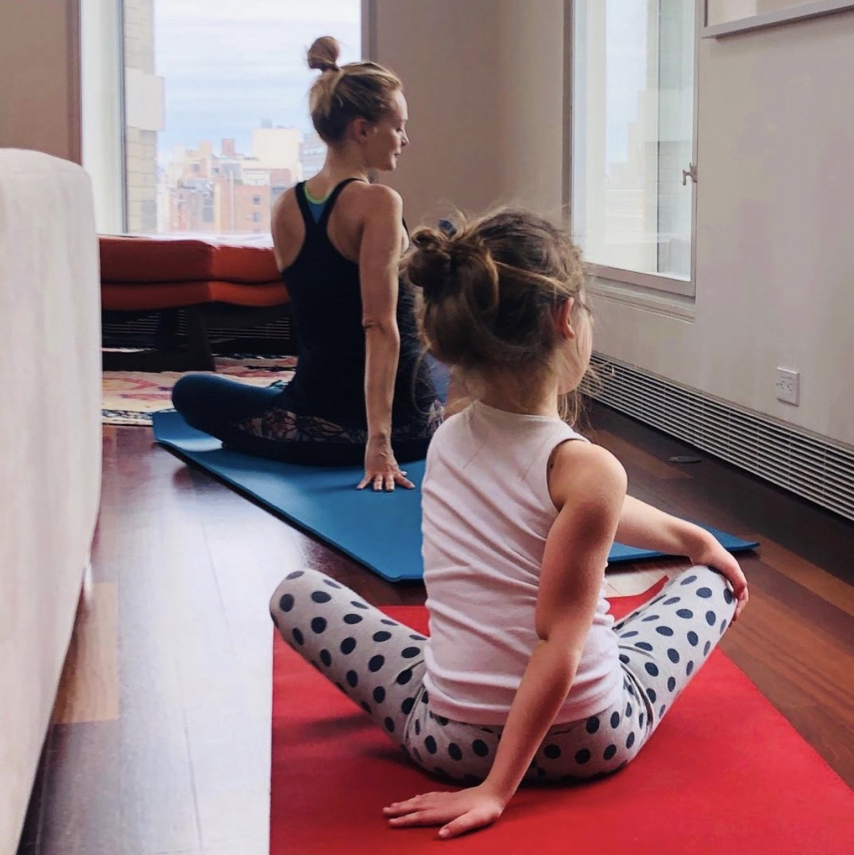 heather graham with her back to the camera doing yoga with a child