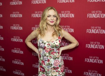 actor heather graham in floral dress and hands on hips on red carpet