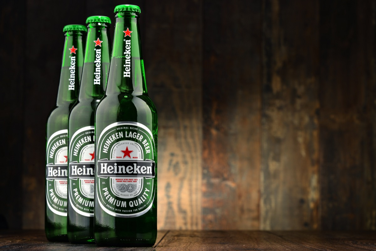 three green bottles of heineken beer on wooden background