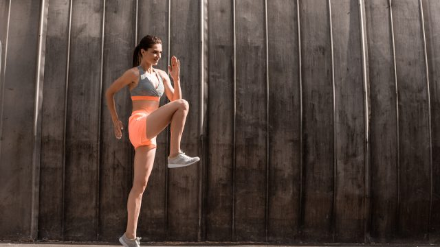 sportive young woman doing front knee lifts or running on the spot while walking