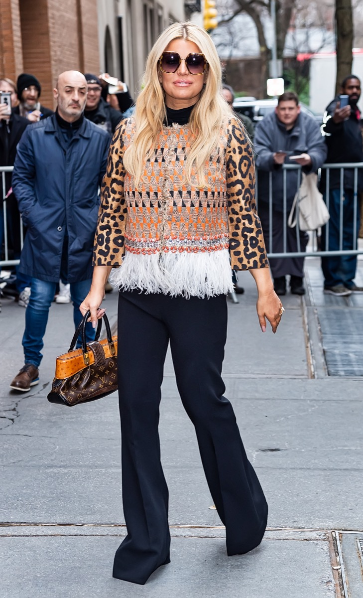 jessica simpson in black pants, leopard top, and fringe vest with louis vuitton bag on street