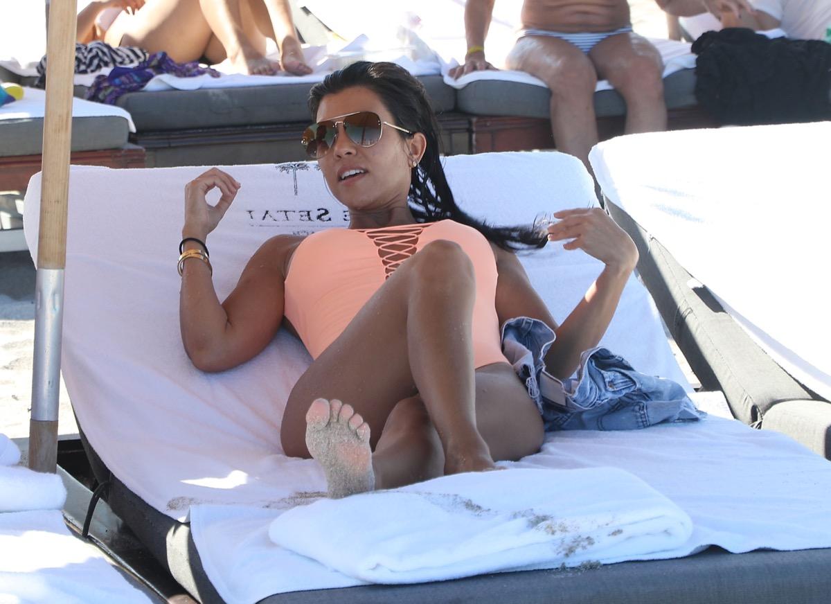 kourtney kardashian in pink swimsuit on lounge chair