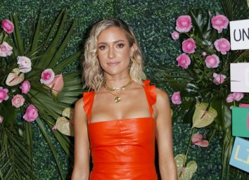 kristin cavallari in orange dress on red carpet in front of green floral and grass wall