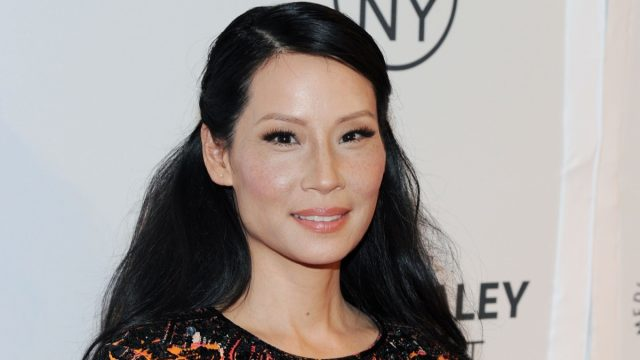 lucy liu with her hair half up, half down in front of white step-and-repeat