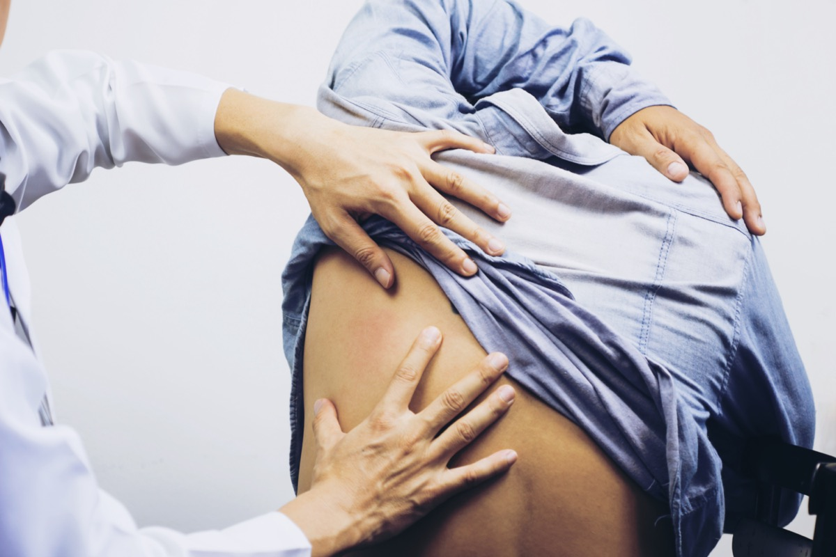 A male physiotherapist examining mans back in the medical office.