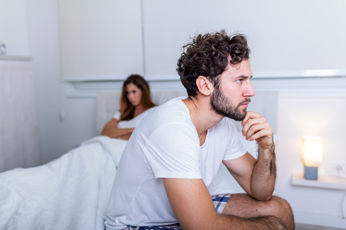 Sad man sitting on a bed, girlfriend in the background.