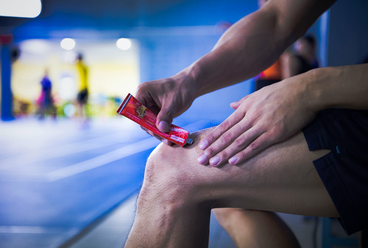 A fitness man applying ointment cream (lotion) onto his knee to relieve the pain or injury