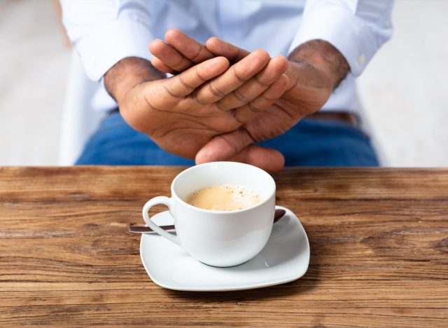 picture of man putting two hands out to refuse a cup of coffee
