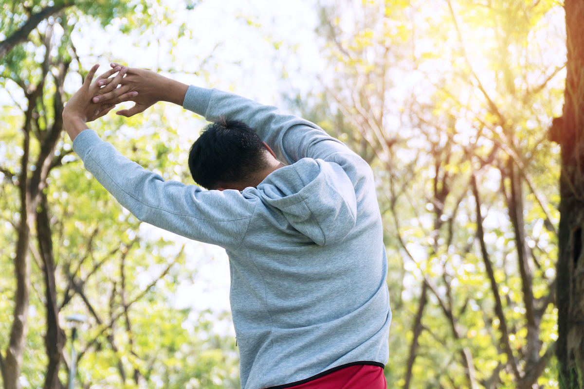 Back of athlete young man stretching arm shoulder before workout in the park. Trainer male warming up preparation body before running at outdoor. Healthy lifestyle concept.