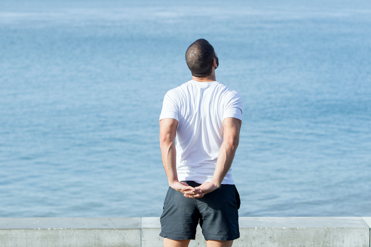 Strong Man Stretching Arms Behind Back at Sea