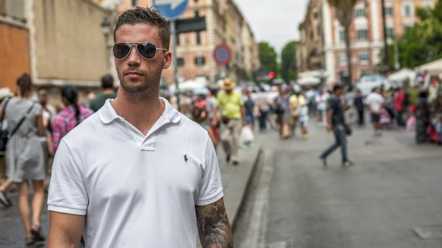 Rome, Italy - July 13th 2015: Cool handsome young caucasian man wearing sunglasses and a white t-shirt standing with confidence and style in a busy street as people walk past on the road and sidewalk
