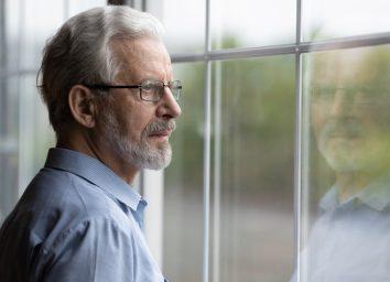 Senior man in eyeglasses looking in distance out of window