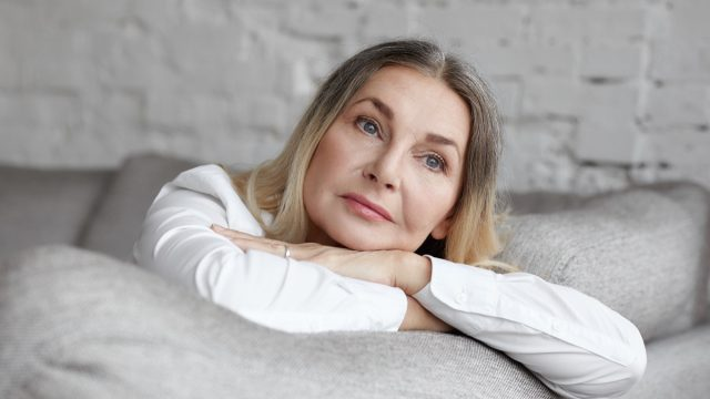 Middle aged woman with long straight hair resting on grey comfortable sofa, having sad unhappy expression.