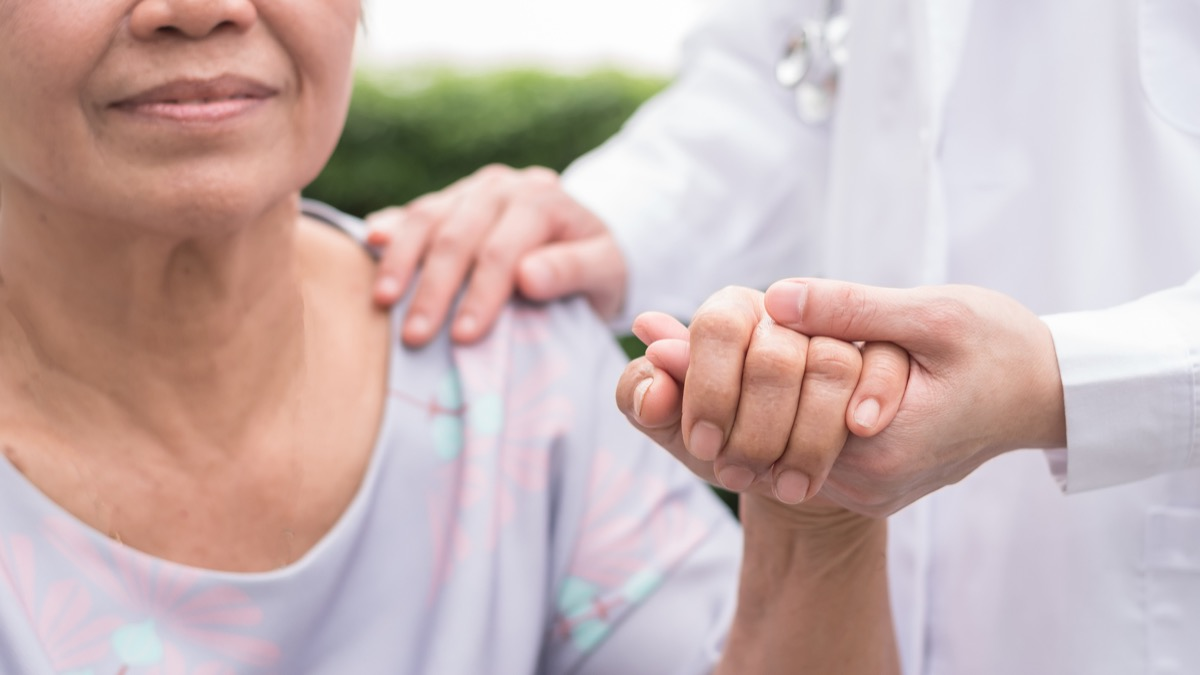 Elderly senior dementia patient in nursing hospice home holding geriatrician doctor's hand