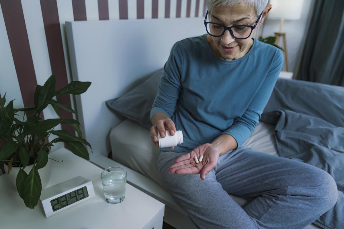 Mature woman taking melatonin supplement pill before bed