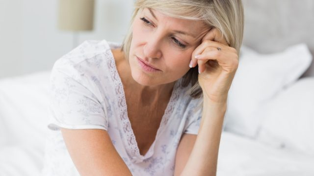 Mature woman sitting in bed at home.