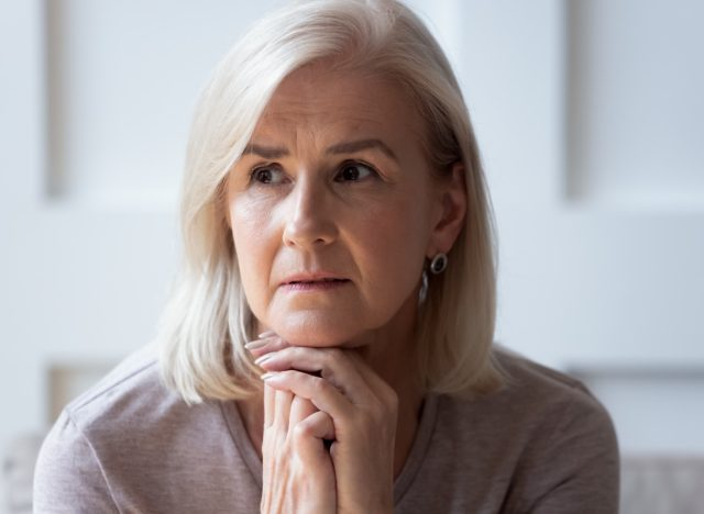 Mature woman sitting upset at home.