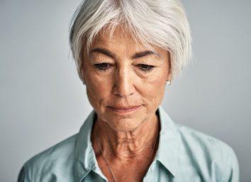 Senior woman posing against a grey background.