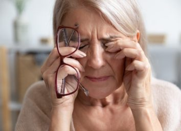 Mature woman takes off her glasses and massages eyes.
