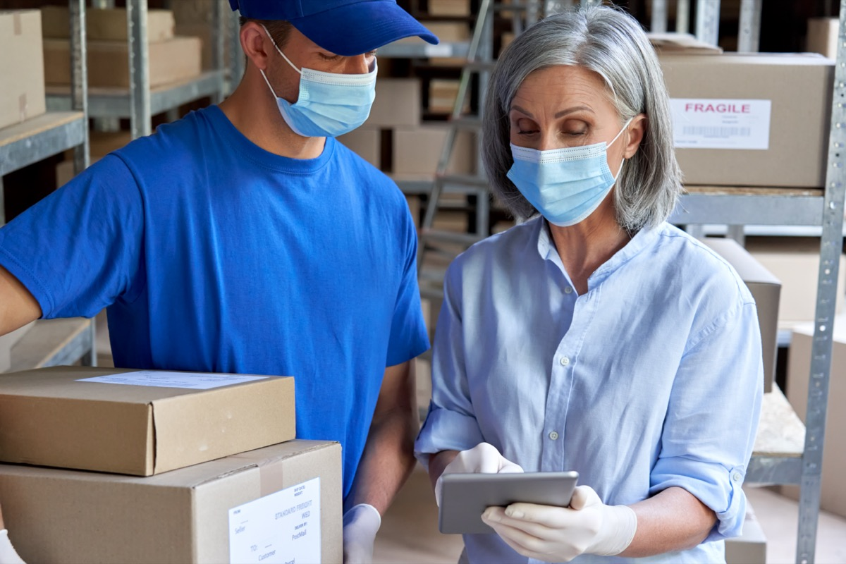 Female supervisor wearing face mask using digital tablet in warehouse talking to male courier holding shipping parcels boxes delivering packages.