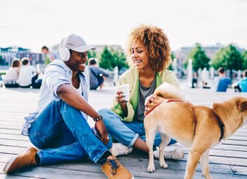 Cheerful afro american male and female hipster joking and having fun sitting on square with cute dog, romantic couple in love laughing during first date on sunny spring day talking to each other