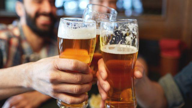 men drinking beer at a bar