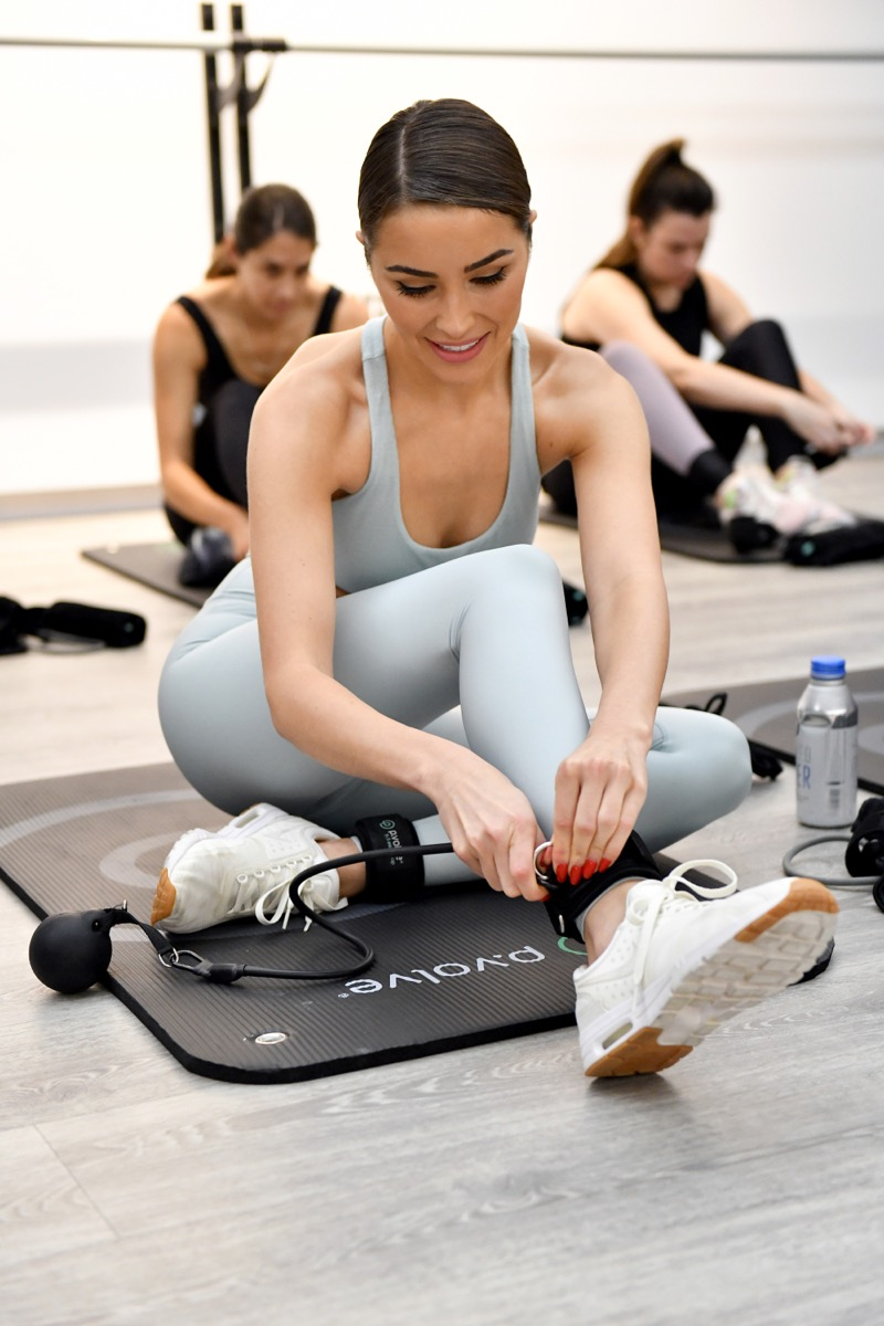 olivia culpo in gray workout gear lacing sneakers